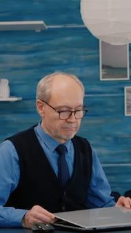 Starszy mężczyzna, freelancer, otwierający laptopa, mrużąc oczy podczas czytania e-maili