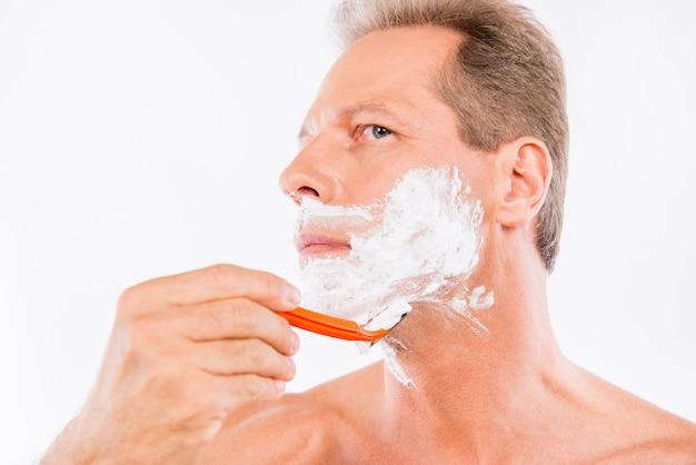 Starszy mężczyzna goli brzytwą