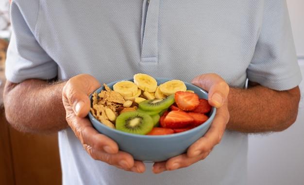 Starszy mężczyzna gotowy do spożycia sałatki ze świeżych i suszonych owoców. pora śniadania lub obiadu, zdrowe odżywianie