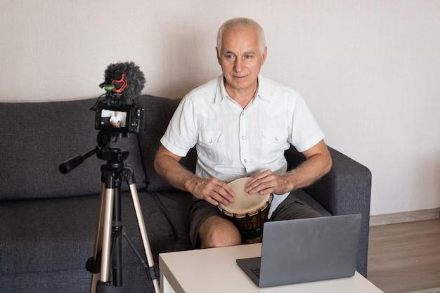 Starszy mężczyzna gra na bębnie w domu i nagrywanie wideo na blogu