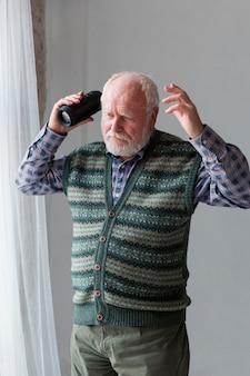 Starszy mężczyzna gra piosenki na głośnik