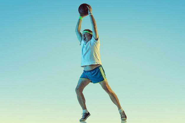 Starszy mężczyzna gra w koszykówkę na gradientowym tle w świetle neonu. model kaukaski w świetnej formie pozostaje aktywny, wysportowany.