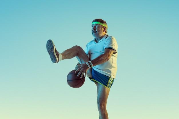 Starszy mężczyzna gra w koszykówkę na ścianie gradientu w świetle neonu. model kaukaski w świetnej formie pozostaje aktywny, wysportowany. pojęcie sportu, aktywności, ruchu, dobrego samopoczucia, zdrowego stylu życia.