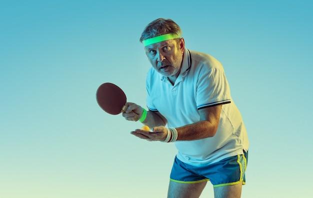 Starszy mężczyzna gra w tenisa stołowego na ścianie gradientu w świetle neonu