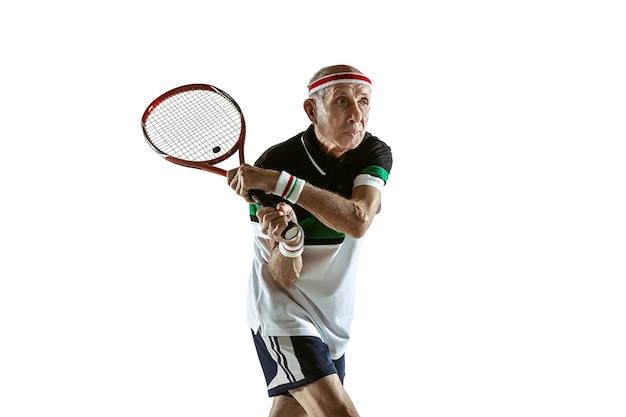 Starszy mężczyzna grający w tenisa w odzieży sportowej na białej ścianie