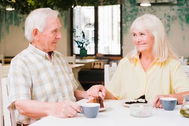 Starszy mężczyzna i jedzenie deserów pijących gorące napoje