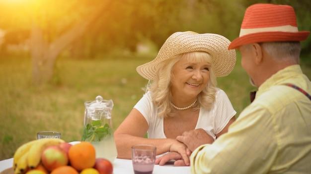 Starszy mężczyzna i kobieta siedzą przy stole w malowniczym ogrodzie i patrzą sobie w oczy