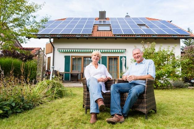 Starszy mężczyzna i kobieta siedzi przed domem