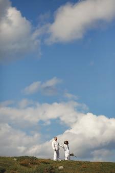 Starszy mężczyzna i kobieta w górach. kobieta z koszem kwiatów. mężczyzna w białej koszuli.