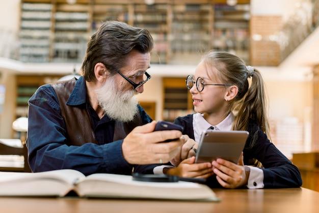 Starszy mężczyzna i mała śliczna dziewczyna siedzą razem w zabytkowej bibliotece, porównują książki, smartfon i nowe urządzenie do czytania książek cyfrowych. dziadek i wnuczka w bibliotece