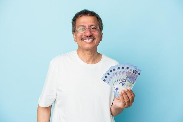 Starszy mężczyzna indian gospodarstwa rachunek na białym tle na niebieskim tle szczęśliwy, uśmiechnięty i wesoły.