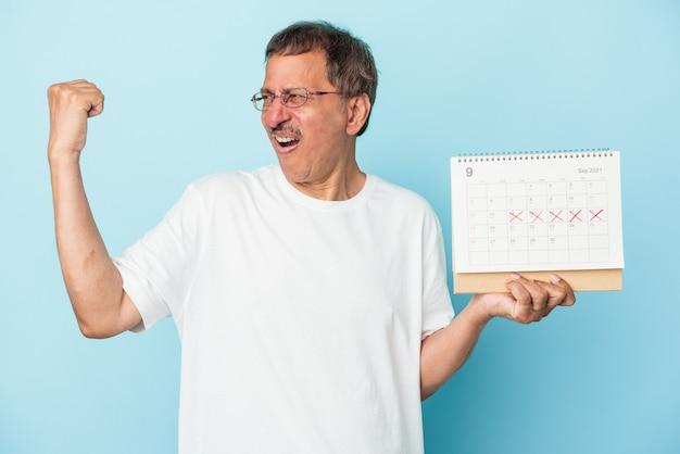 Starszy mężczyzna indian trzyma kalendarz na białym tle na niebieskim tle podnosząc pięść po zwycięstwie, koncepcja zwycięzca.