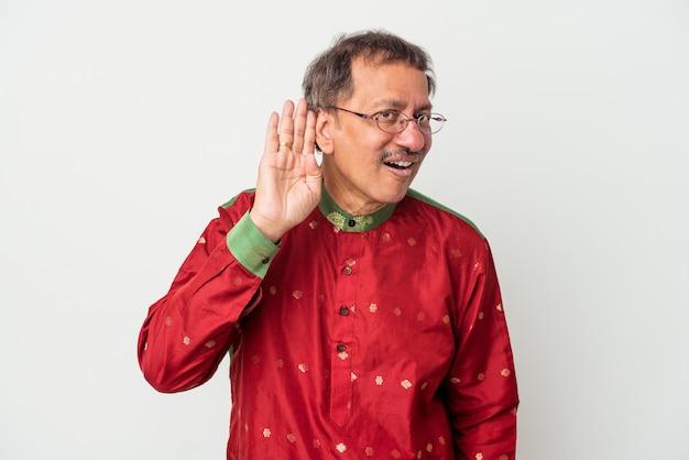 Starszy mężczyzna indian ubrany w strój indyjski na białym tle próbuje słuchać plotek.