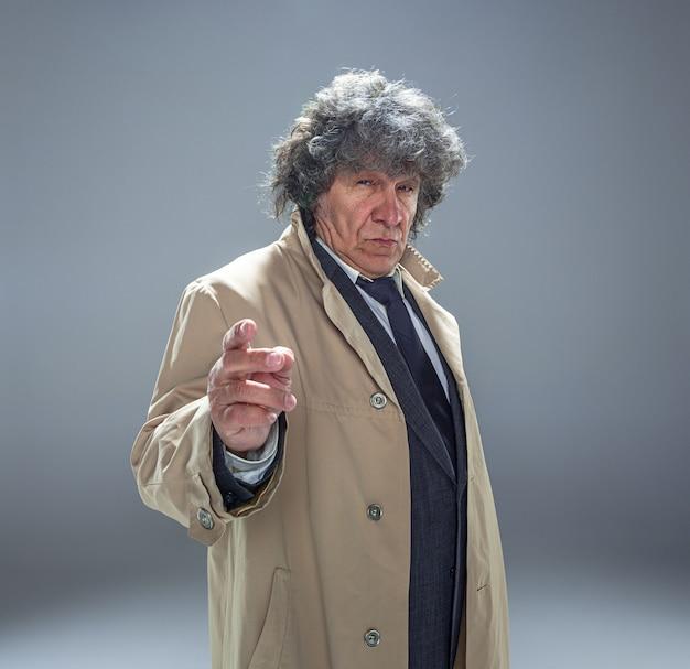 Starszy mężczyzna jako detektyw lub szef mafii na szarej przestrzeni studia