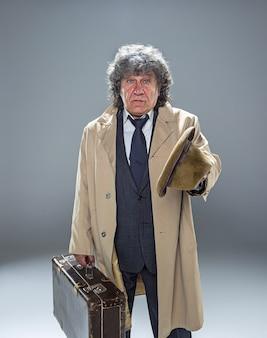 Starszy mężczyzna jako detektyw lub szef mafii w szarym studio
