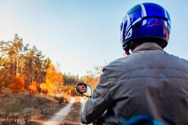 Starszy mężczyzna jazda skuterem na jesień leśnej drodze. kierowca w kasku jeździ na motorowerze. widok z tyłu
