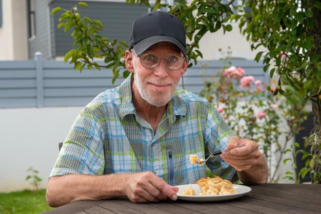 Starszy mężczyzna je tort outdoors