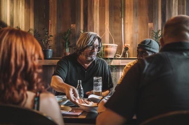 Starszy mężczyzna jedzący obiad z przyjaciółmi w restauracji?