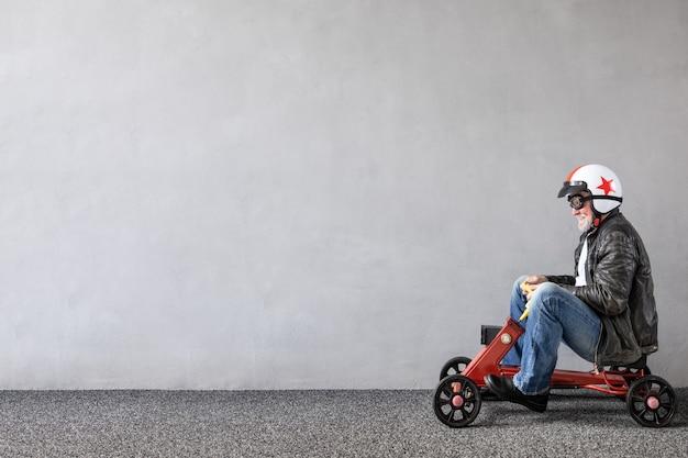 Starszy mężczyzna jedzie autko. pełnej długości portret zabawny biznesmen przed betonową ścianą z miejsca na kopię. koncepcja uruchomienia firmy