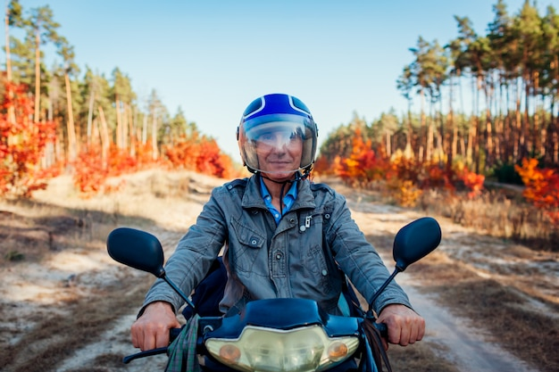 Starszy mężczyzna jedzie hulajnoga na jesieni lasowej drodze. kierowca w kasku na motorowerze