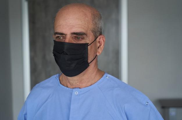 Starszy mężczyzna jest ubranym maskę podczas wybuchu koronawirusa i grypy