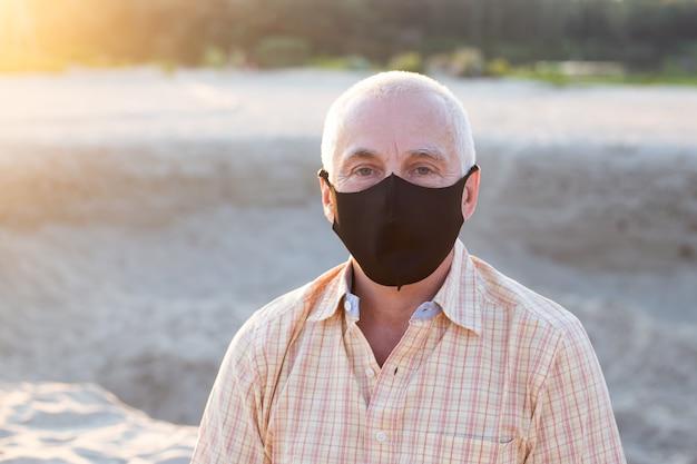 Starszy mężczyzna jest ubranym medyczną maskę ono chroni przed coronavirus, medycznym i zdrowie pojęciem