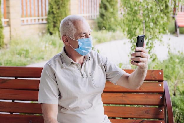 Starszy mężczyzna jest ubranym medyczną maskę z smartphone. koncepcja koronawirusa. ochrona dróg oddechowych