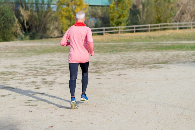 Starszy mężczyzna jest ubranym szkła jogging przy parkiem