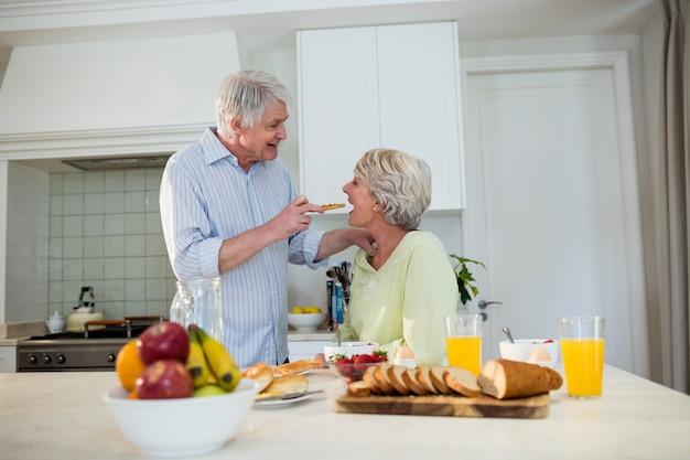 Starszy mężczyzna karmi starszą kobietę