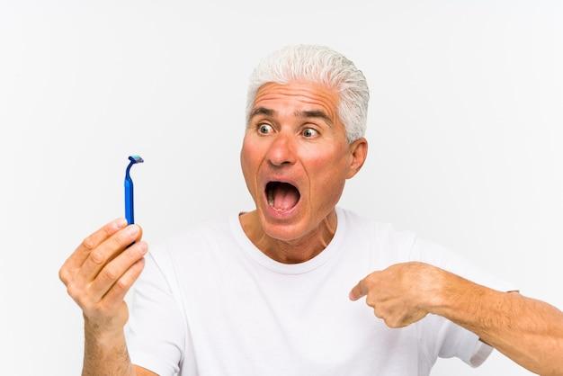 Starszy mężczyzna kaukaski trzymający żyletkę na białym tle zaskoczony, wskazując na siebie, uśmiechając się szeroko.