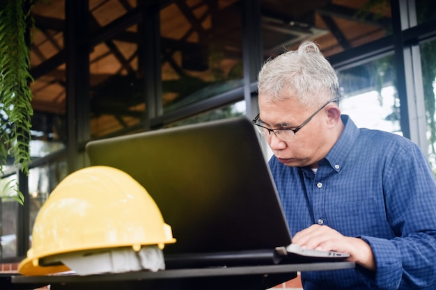 Starszy mężczyzna korzysta z pracy komputera z dala od domu, pozostając w domu, zachowaj bezpieczeństwo
