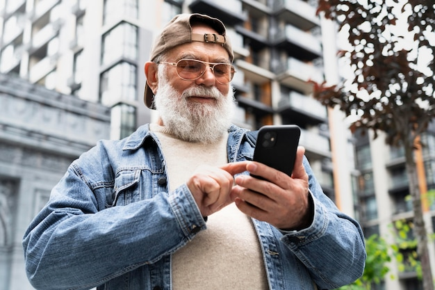 Starszy mężczyzna korzystający ze smartfona na zewnątrz w mieście