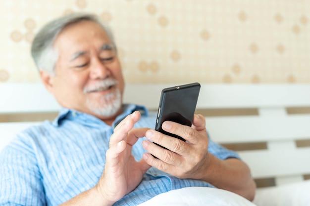 Starszy mężczyzna korzystający ze smartfona, uśmiechnięty, czuje się szczęśliwy w łóżku w domu - koncepcja seniora stylu życia - wybierz fotografię ostrości i rozmycia