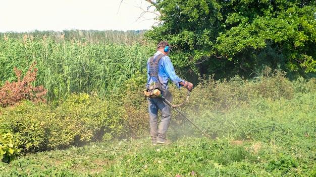 Starszy mężczyzna kosi trawę z kosą spalinową. mężczyzna ubrany w kombinezon roboczy, okulary ochronne, dźwiękoszczelne słuchawki i rękawice robocze.