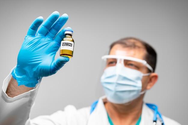 Starszy mężczyzna lekarz lub naukowiec trzymając fiolkę szczepionki z bliska