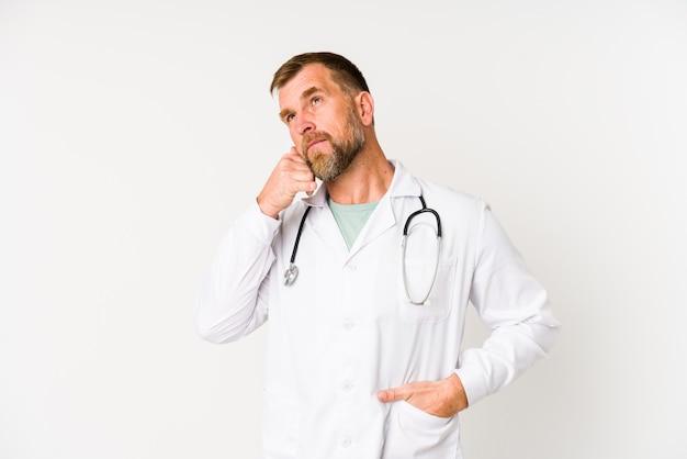 Starszy mężczyzna lekarz na białym tle na białej ścianie przedstawiający gest połączenia telefonu komórkowego z palcami.