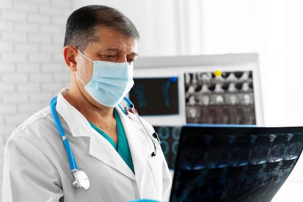 Starszy mężczyzna lekarz w masce bada głowę mri w szpitalu z bliska