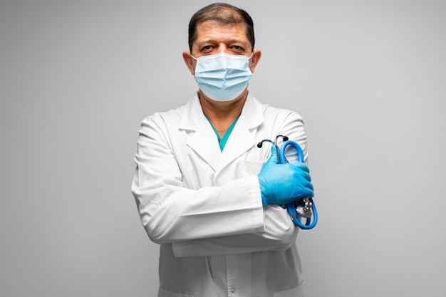 Starszy mężczyzna lekarz w masce stojącej przed szarym tle portret