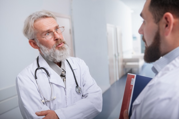 Starszy mężczyzna lekarz wyglądający na zaniepokojonego, rozmawia ze swoim kolegą z kliniki