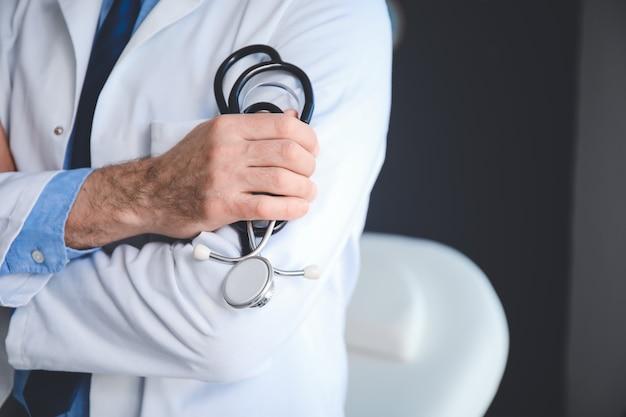 Starszy mężczyzna lekarz ze stetoskopem w klinice, zbliżenie