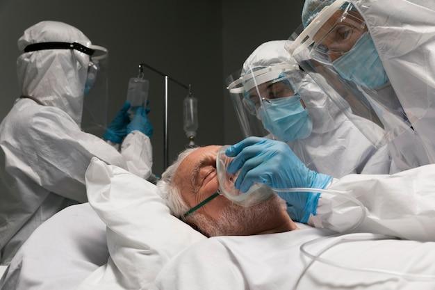 Starszy mężczyzna leżący chory w szpitalnym łóżku obok lekarzy