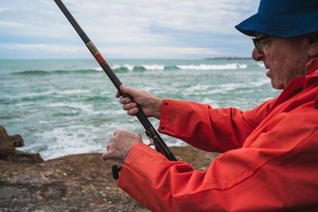 Starszy mężczyzna łowi w morzu.