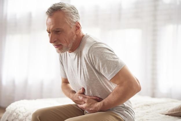 Starszy mężczyzna ma ból brzucha w łóżku rano.