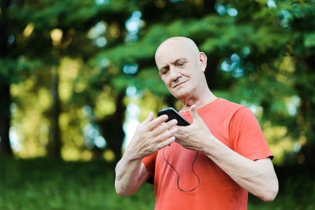 Starszy mężczyzna ma na sobie słuchawki i słuchanie muzyki na swoim smartfonie w parku.