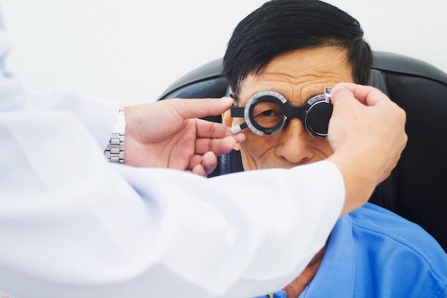 Starszy mężczyzna ma oczy badane przez lekarza okulistę na narzędzia do badań w nowoczesnej klinice