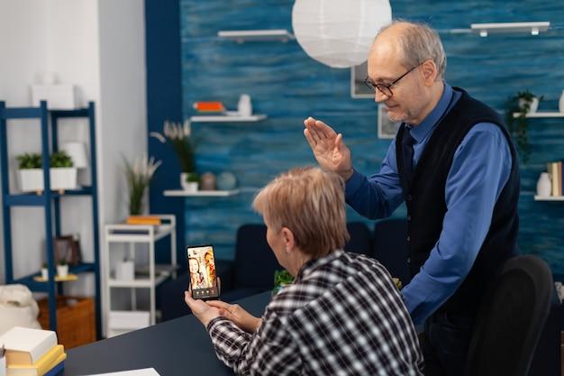 Starszy mężczyzna macha do kamery smartfona podczas rozmowy wideo z krewnymi