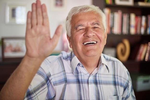 Starszy mężczyzna macha do kamery