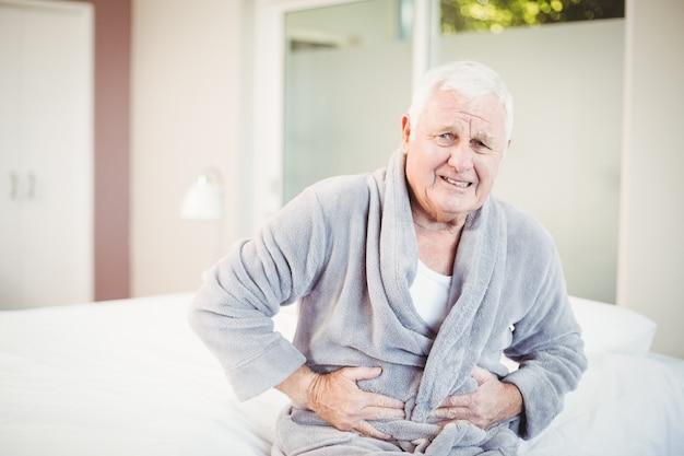 Starszy mężczyzna marszczy brwi z bólem brzucha
