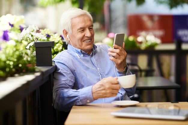 Starszy mężczyzna mówi przez połączenie wideo w kawiarni