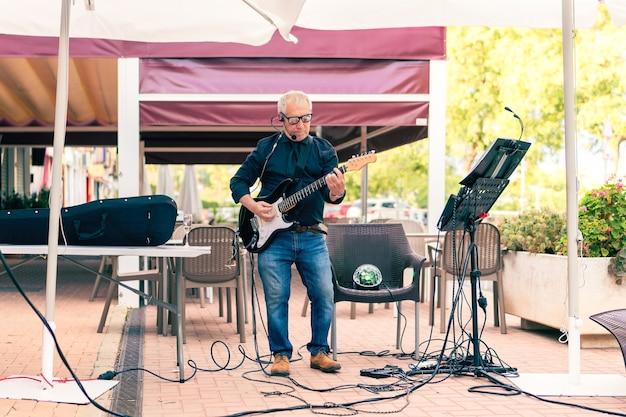 Starszy mężczyzna muzyk grający na gitarze elektrycznej na tarasie z publicznością